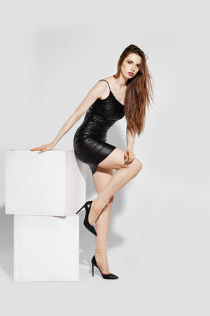 Low angle view of a girl in tulle socks and eco leather short dress