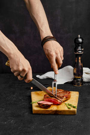 Cutting juicy steak on wooden cutting board over black background