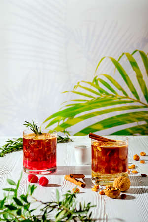 Refreshing espresso and tonic summer drinks on white table under hard sulight