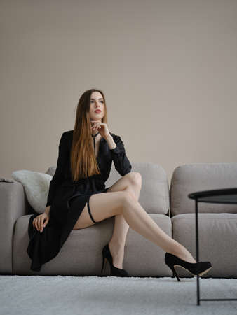 Full length portrait of lovely young woman in short dress and play strap suit Banque d'images