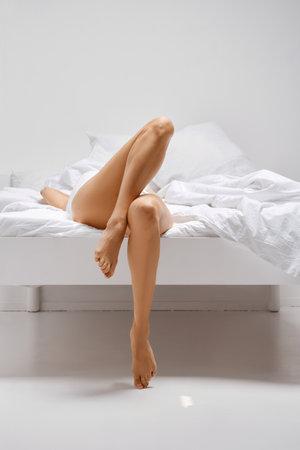 Slender female legs on the edge of the bed Imagens