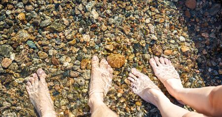 shallow water: Male and female feet in shallow water Stock Photo