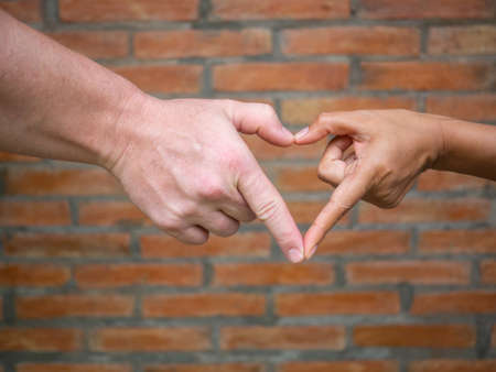 Close-up of making heart shape with hands between man and woman with brick background. Love Concept.