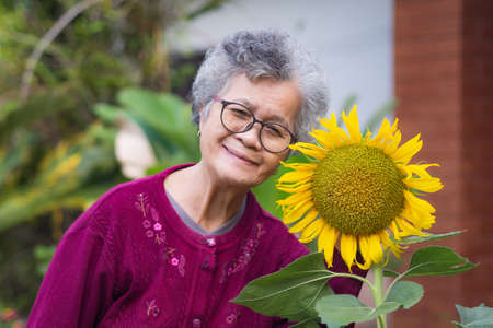 Senior woman short white hair standing beside the sunflower and smiling in the garden. Asian elderly woman healthy and have positive thoughts on life make her happy every day. Health concept