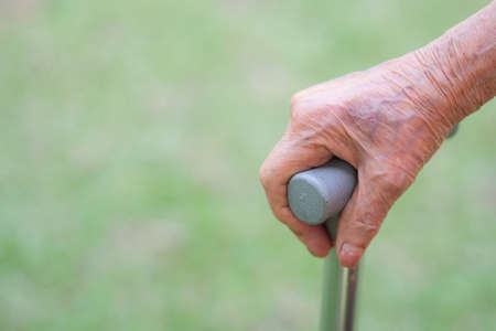 Close-up of elderly woman hand holding a walking stick standing in the garden. Space for text. Health care concept
