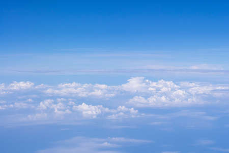 Bright blue sky and white clouds. Beautiful above sky panoramic view from the window of an airplane flying in the clouds. Feeling freedom and new inspiration. Skyline background with copy space.