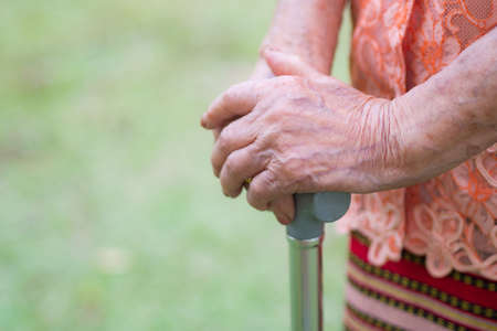 Close-up of elderly woman hands holding a walking stick standing in the garden. Space for text. Health care concept