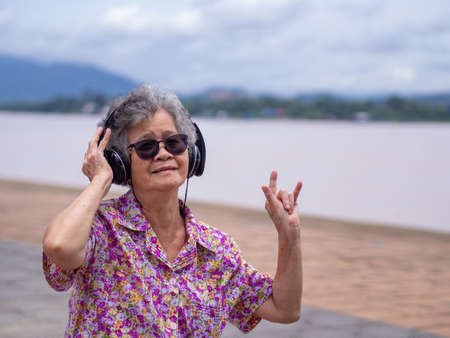 Portrait of happy senior woman wearing sunglasses and hand show i love you.