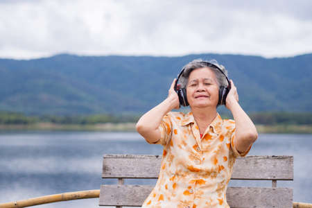 Portrait of happy elderly woman listening music on headphone for relaxing with side the lake. Relaxing time concept. Фото со стока
