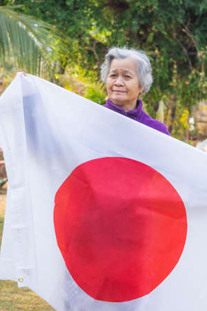 Portrait of elderly woman with short white hair holding Japanese flag, standing in her garden. Фото со стока