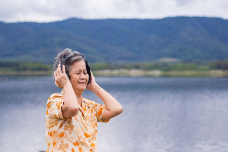 Portrait of happy senior woman listening music on headphone for relaxing with side the lake. Relaxing time concept.