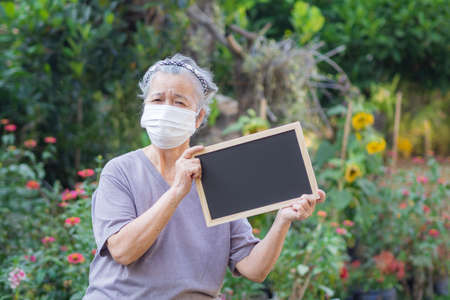 Portrait of elderly woman standing holding a blackboard and wearing face mask for healthy because have air pollution PM 2.5. Mask for protect Virus, Bacteria, Pollen Grains. Healthcare concept 版權商用圖片