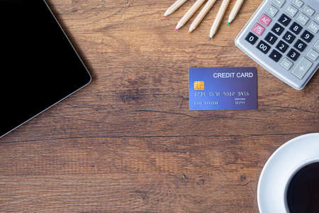 Top view of a blue credit card, pencil, calculator, coffee cup and tablet on wooden table in office. Space for text. Wood texture background. Business and finance concept Foto de archivo