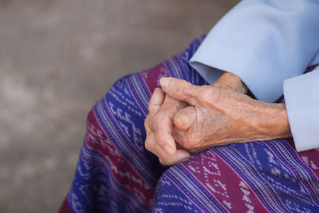 Close-up of elderly woman's hands joined together. Focus on hands wrinkled skin. Health care concept