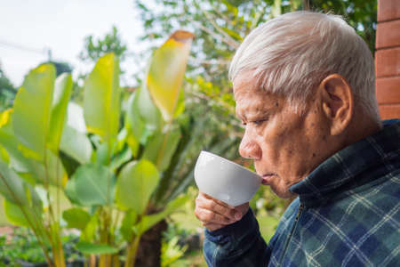 An elderly man drink coffee morning in his garden. 스톡 콘텐츠