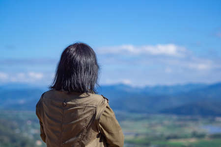 Back view of a woman person stands alone looking at mountains. Travel concept. Back View.