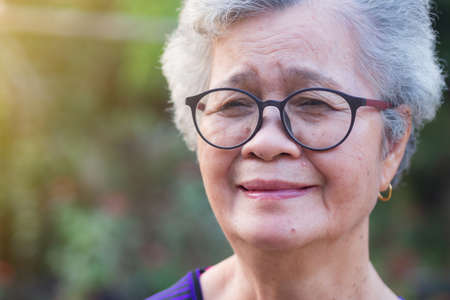 A portrait of an elderly woman wearing eyeglasses, smiling and looking at the camera while standing in a garden. Space for text. Concept of old people and healthcare