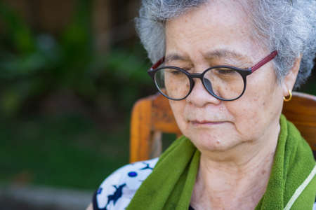 Close-Up Portrait Of Senior Woman Outdoors. Asian elderly woman wearing glasses and eyes closed sitting on chair in the garden. Beautiful woman short hair with grey hair and healthy Foto de archivo