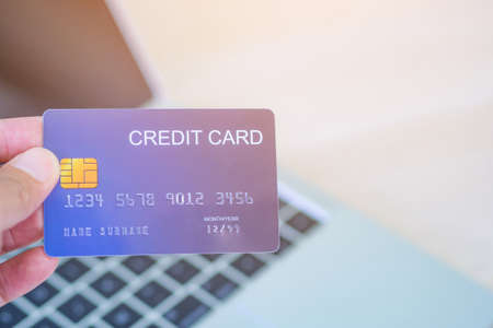Close-up photo of left hand woman holding blue credit card mockup with a laptop background and copyspace on the right side for text. Easy e-commerce shopping online and payment by credit card