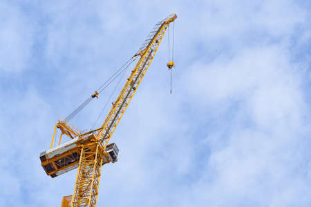 Construction site with cranes on sky background. Big yellow machinery construction crane tool of building industry for heavy lifting on blue sky background. Business engineering equipment modern
