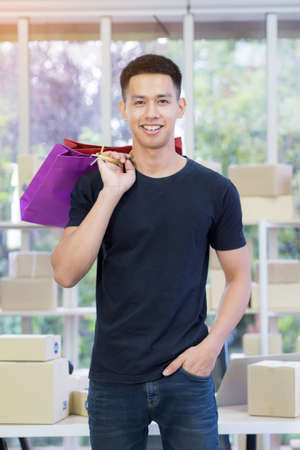 Asian young man wearing black t-shirts and blue jeans stand smiling, a right hand carrying a multicolored bag taking picture in the office after returning from shopping. Business e-commerce concept Stock Photo
