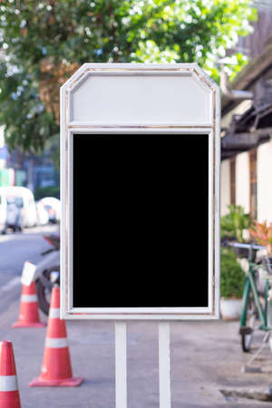 Blank black billboard with white frame ad vertical laying on the side of the road. Signboard for public relations media, advertising, marketing. Space for text