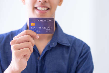 Close-up of the right hand of a young man holding a blue credit card, seeing a smile but not seeing the face clearly. Wearing a blue casual shirt and prepare for shopping online with a credit card