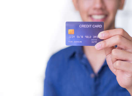 Close-up of the left hand of a young man holding a blue credit card, seeing a smile but not seeing the face clearly. Wearing a blue casual shirt and prepare for shopping online with a credit card