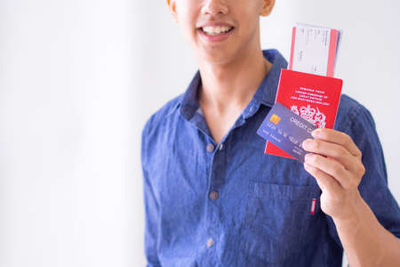 Close-up of the left hand of a young man holding a blue credit card, passport and plane ticket, seeing a smile but not seeing the face clearly. He's wearing a blue shirt and prepare for go to travel