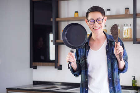 Young man's standing holding the pan and ladle. He's looking at the camera and smiling in his kitchen for prepared to cook with a happy. Positive thinking for happy life. Happy life concept