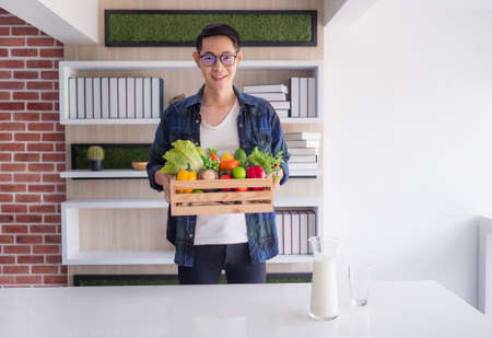 Young man is holding a basket box wooden with colorful vegetables and fruits organic to prepare for foods in the kitchen. Health foods helps to good healthy. Health concept Stockfoto