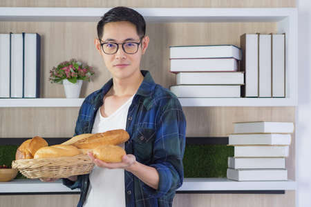 Young man smiling holding a bread at home. Fresh bakery product. Foods concept Banque d'images