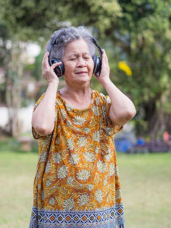 An senior woman standing wearing wireless headphone listening to a favorite song, and smile happy in garden. Asian old woman, short white hair are enjoying the music. Makes her have good mental health