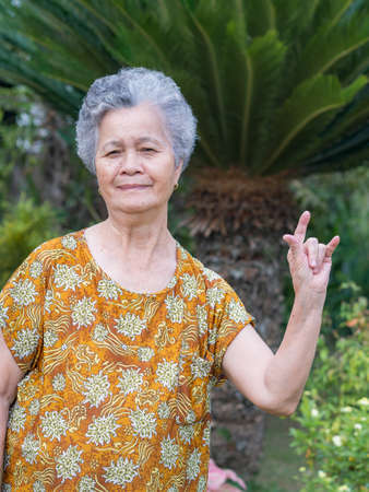 Senior woman with short white hair standing smiling and showing hand sign