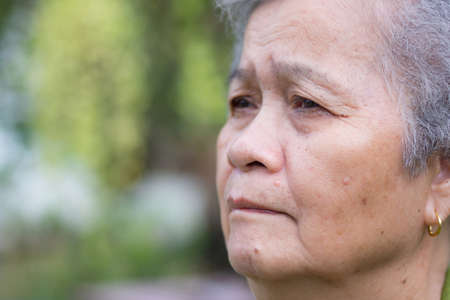 Side view of face senior woman standing and looking away in her garden. Asain elderly will feel lonely than the general person Banque d'images