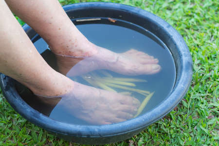 Close-up Of Spa foot with herbs water for relaxation treatment. Senior woman have a ankle pain use herbal treatment to relax the muscles by soaking warm water that is boiled from herbs Stock Photo