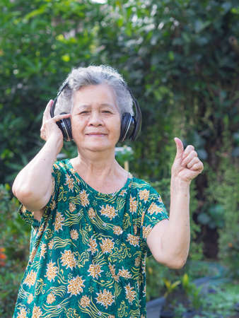 Senior woman standing wearing wireless headphone listening to a favorite song, and smile happy in garden. Asian old woman, short white hair are enjoying the music. Makes her have good mental health