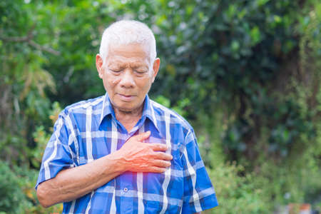 Portrait of elderly man having heart attack. Senior man clutching her chest in pain at the first signs of angina or a myocardial infarction or heart attack. Heart attack concept.