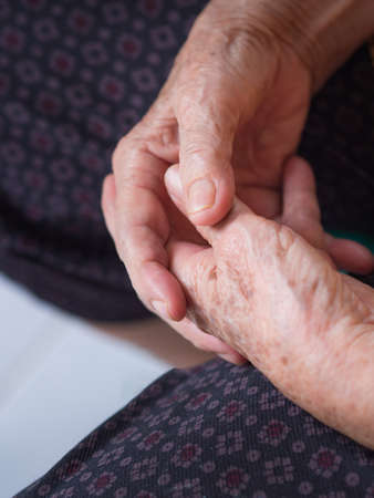 Close-up of an old woman's hands joined, focus on hands wrinkled skin.