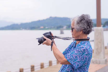 Senior woman taking photo by digital camera at riverside. Elderly woman short white hair, wearing sunglasses, happy when using a camera. Photography concept