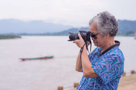 Senior woman taking photo by digital camera at riverside. Elderly woman short gray hair, wearing sunglasses, happy when using a camera. Photography concept