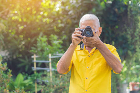 Senior man taking photo by digital camera in the garden. Elderly man wears a yellow shirt, happy when using a camera. Photography concept