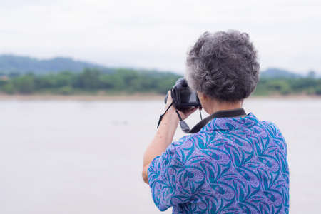 Back view of senior woman taking photo by digital camera at riverside. Elderly woman short gray hair, happy when using a camera. Space for text. Photography concept Reklamní fotografie