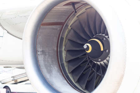 Close-up front view of turbine of jet engine, airplane at airport
