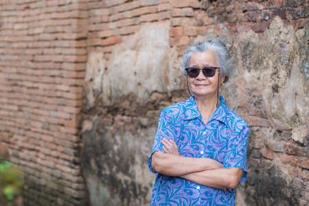 Portrait of elderly woman short white hair, wearing sunglasses, standing and arms crossed on old brick wall background. Holiday and Travel concept.