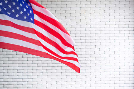 Close-up of the American flag is placed on the left side with copy space on a white brick wall background. 4th of July. Celebrate American National Day. Labor Day. Independence Day. Memorial Day. 写真素材