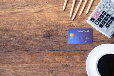 Top view of a blue credit card, pencil, calculator, coffee cup on wooden table in office. Space for text. Wood texture background. Business and finance concept