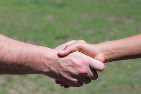 Close-up shot of man shaking hands with woman in the garden