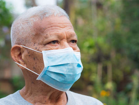 A portrait of an elderly man wearing a face mask looking away while standing in a garden. Mask for protect virus, coronavirus, pollen grains. Concept of old people and healthcare