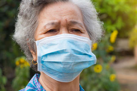 A portrait of an elderly woman wearing a face mask looking away while standing in a garden. Mask for protect virus, coronavirus, pollen grains. Concept of old people and healthcare.